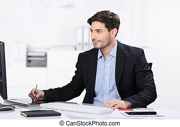Handsome businessman working on a pc