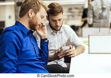 Handsome businessmen using phones in office