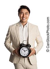 Handsome businessperson holding clock