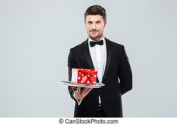Handsome butler in tuxedo with bowtie gift box on tray