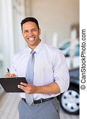car dealership salesman working in showroom