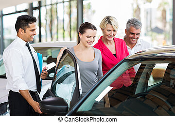 car salesman showing a new car to a family