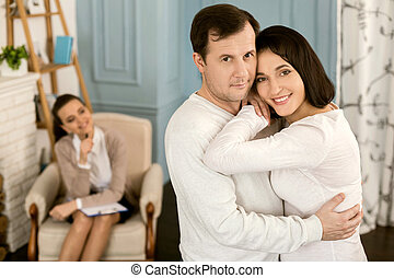 Handsome caring husband hugging his wife