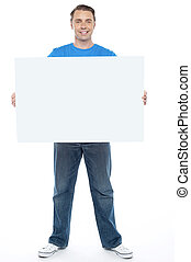 Handsome casual guy holding blank ad board