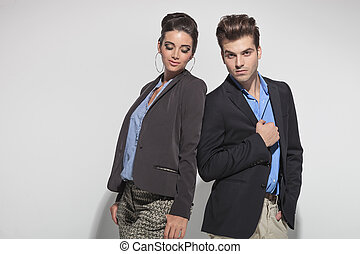 Handsome casual man fixing his jacket while his girlfriend is looking down.