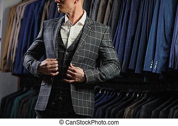 Handsome caucasian businessman dressed in the suit in suit shop