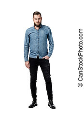Picture of a bearded Caucasian male looking serious while looking towards the camera with one hand in his pocket wearing a blue long sleeves shirt.