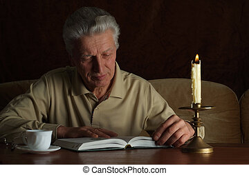 Handsome caucasian man sits at a table with a book on a dark...