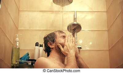 Handsome caucasian man taking shower. 4K close-up shot, warm...