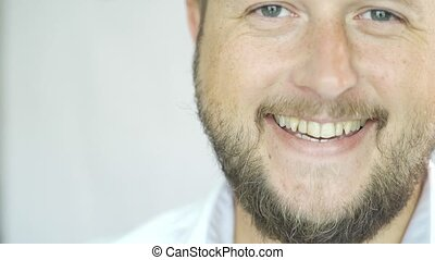 Handsome Caucasian man with a beard smiling on a white background, portrait of a man half face.