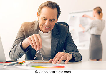 Handsome cheerful man holding a pair of compasses
