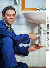 Handsome cheerful plumber repairing sink