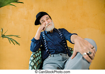 Handsome cheerful trendy senior man with well-groomed beard, wearing dark blue shirt, suspenders, gray pants, and black hipster cap, sitting in chair in studio in front of yellow wall with palm tree