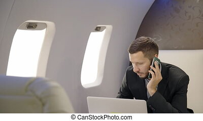 Handsome chief banker director businessman is making call, working with laptop sitting in airplane interior.