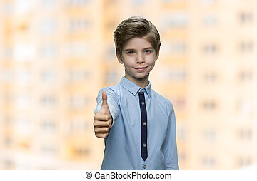 Handsome child boy showing thumb up sign.