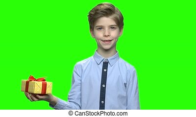 Handsome child holding yellow gift box with red ribbon.
