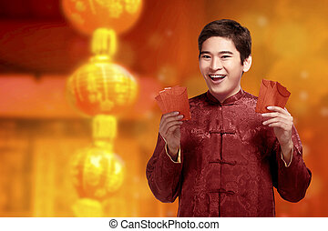 Handsome chinese man with cheongsam clothes showing red envelopes on his hands