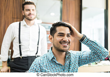 Handsome Client Examining Freshly Cut Hair In Barber Shop