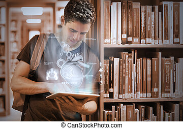 Handsome college student working on his digital tablet pc with futuristic interface in university library