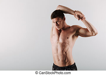 Handsome concentrated young sportsman make stretching...