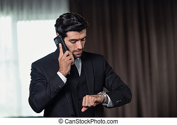 Handsome confident businessman delayed checking the time in the watch while he is making a telephone call with his mobile phone