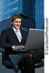 Handsome confident businessman working on his laptop in front of office building