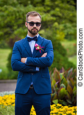 Handsome confident groom in a blue suit and sunglasses posing in the park