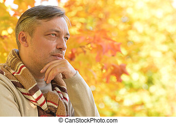 Handsome confident man posing, autumn leaves on background...