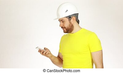 Handsome construction engineer or architect in yellow tshirt talking on his cell phone against white background. 4K video