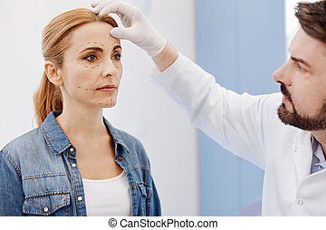 Handsome cosmetic surgeon examining his patients face