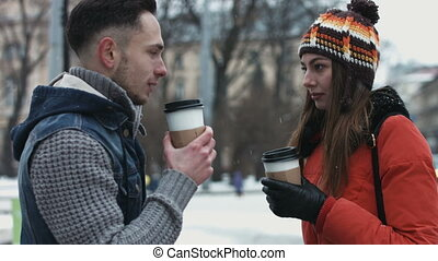 Handsome couple of thier first date. Young male and woman talking and drinking coffee-to-go outdoors.