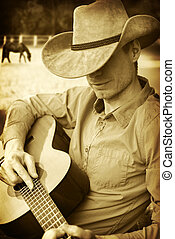 Handsome man in cowboy hat playing guitar on ranch. Monochrome image