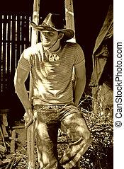 cowboy - handsome cowboy sitting on a ladder in barn looking...