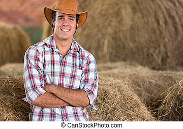 cowboy standing against hay bales