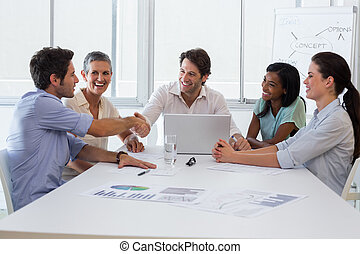 Handsome coworkers shaking hands in approval - Handsome...