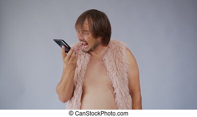 Handsome crazy guy with a beard and in a pink fur coatfrom, talking on the phone