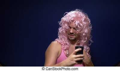handsome crazy guy with a beard and in a pink wig makes sephi from a smartphone. dark background.