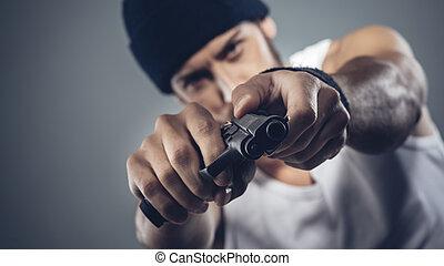 Handsome criminal holding a gun