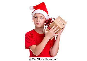 Handsome curious boy, santa hat on his head, checking the gift box. Concept: christmas or Happy New Year holiday