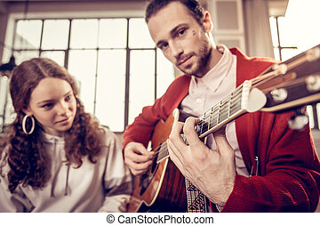 Handsome dark-eyed older brother playing the guitar for sister