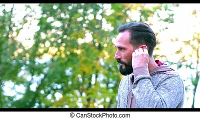 Handsome Dark-Haired Man is Listening to Music in Summer Park