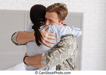 Handsome delighted soldier hugging his wife