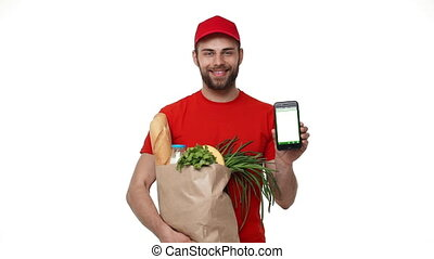 Handsome delivery man showing mobile phone on white background