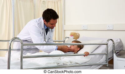 Handsome doctor checking on little girl in the hospital ward