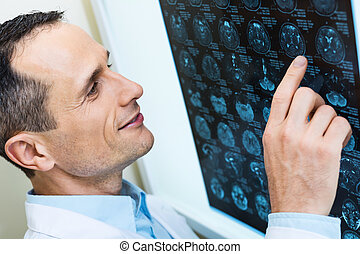Handsome doctor comparing computer tomography results