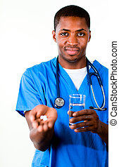 Handsome doctor in scrubs with pills and glass of water