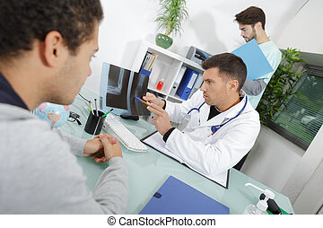 handsome doctor is talking to male patient and showing x-ray