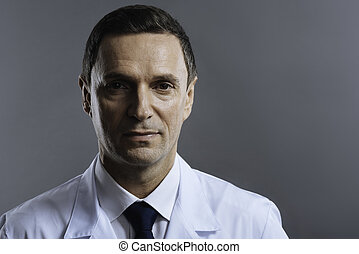 Handsome doctor posing on a grey background
