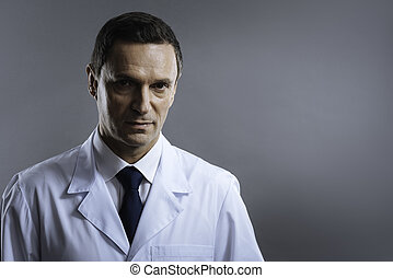 Handsome doctor standing on a grey background