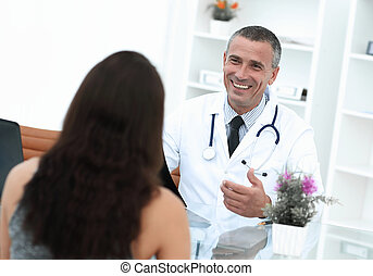 Handsome doctor talking with his patient